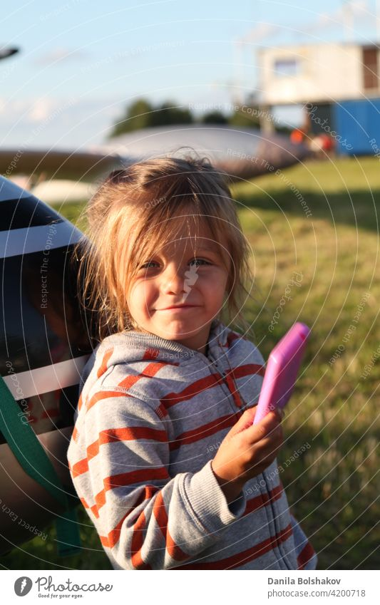 Child plays photographer outdoors. Girl imagines taking pictures on pink plastic toy phone beauty smile lawn hobby concept enjoy shot grass positive fashion