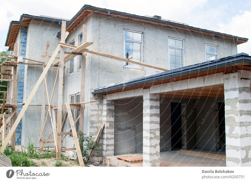 facade of cottage under construction with new inserted windows house home site brick extension architecture work wall roof build building modern apartment