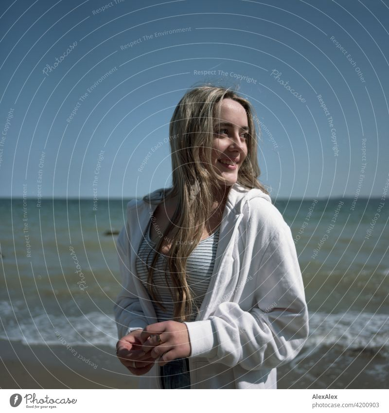 Analogue rectangular image of a beautiful blonde girl standing on the beach of the Baltic Sea and looking to the side Girl Smiling joyfully Landscape by Blonde