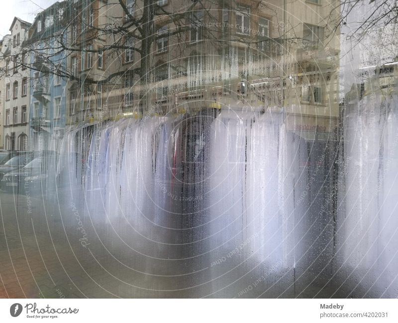 Reflection of a row of houses in the fogged window of a dry cleaner and laundry in the district of Bockenheim in Frankfurt am Main in the German state of Hesse