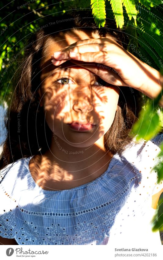Play of light and shadow portrait of a beautiful tanned caucasian cute girl in the tropical greenery. Travel, vacation, warm countries. female nature summer