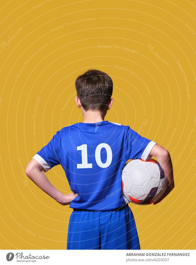 back boy with soccer ball and clothes on a yellow isolated background kid football sport holding game player activity goal athlete action youth training