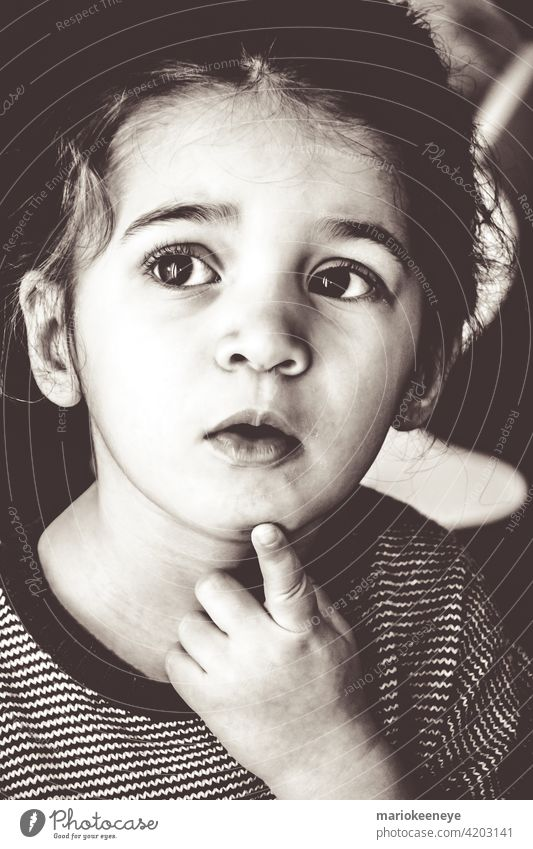 Black and white portrait of a Caucasian little girl in a pensive attitude individuality innocence black and white serene tranquility contemplation loneliness
