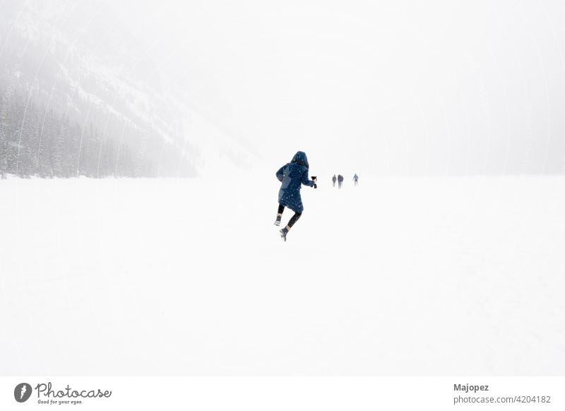 Young person jumping in the air in a winter landscape with snow. Frozen Lake Louise, Banff National Park, Alberta, Canada nature beautiful freedom outdoor