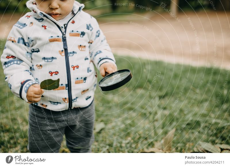 Child playing with magnifying glass 1 - 3 years Caucasian Magnifying glass explore Curiosity Happy Happiness Colour photo Nature Joy Infancy Lifestyle