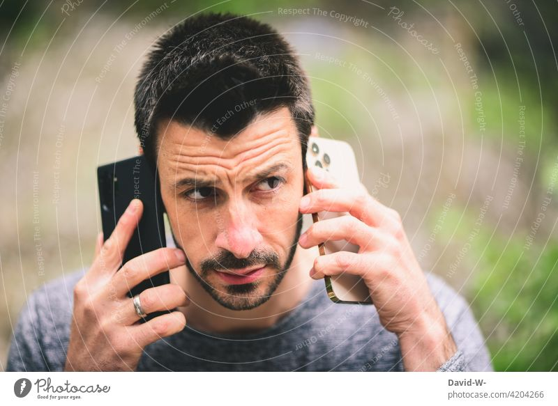 Conference call via smartphone Cellphone make a phone call multitasking Man conversation two Mobile phones conference call