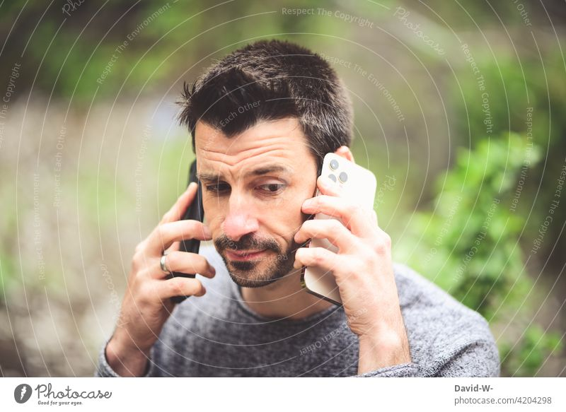 making calls with two mobile phones - mulitasking Mobile phones make a phone call multitasking Stress Man Cellphone conversation Dual listen reachability