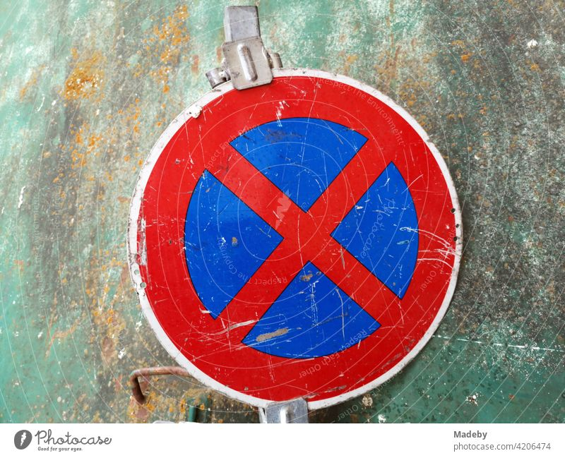 Strict no stopping in front of a yellowed green glass container in Offenbach on the Main in Hesse No standing Transport Road sign Sign symbol symbolism Red Blue