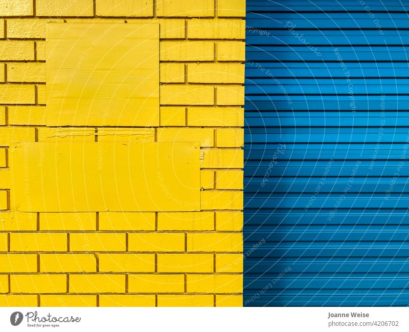 Yellow brick wall and blue roller door. blue and yellow yellow wall blue door Blue Door Colour photo Exterior shot Day Metal Architecture Building