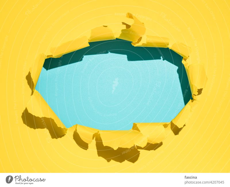 Torn yellow background, copy space paper torn hole rip ripped through sheet page break circle oval open edge wall blue empty blank frame bright background