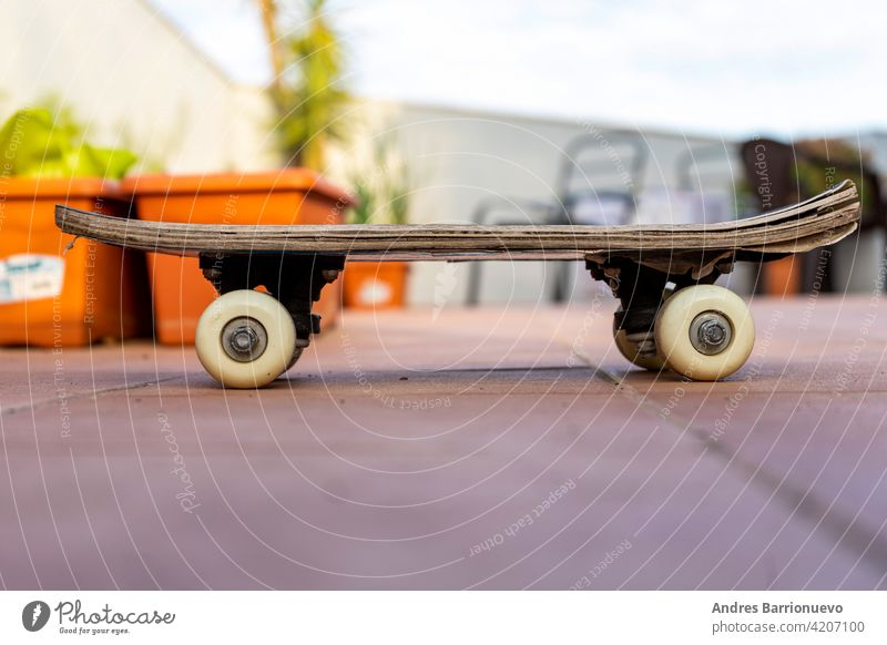 View of an old skateboard on the terrace of the house. Selective focus skateboarding extreme concrete surfing wheel view leisure side paint high enjoyment