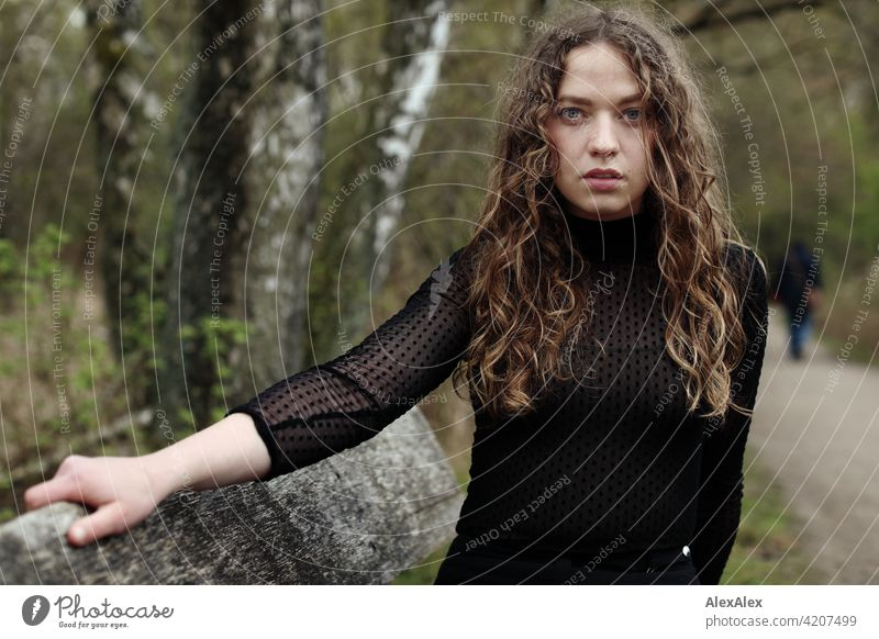 Portrait of a young woman with long, brunette, curly hair in front of a moor landscape on a bench Woman Young woman 18 - 30 years pretty Beauty & Beauty