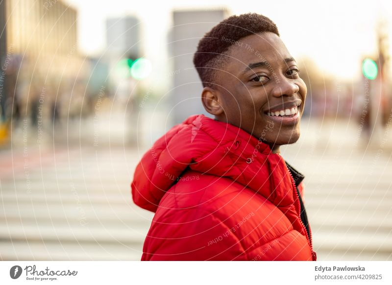 Portrait of a young man standing in a city street, smiling black outside urban millennial African outdoors Warsaw one real people casual lifestyle guy