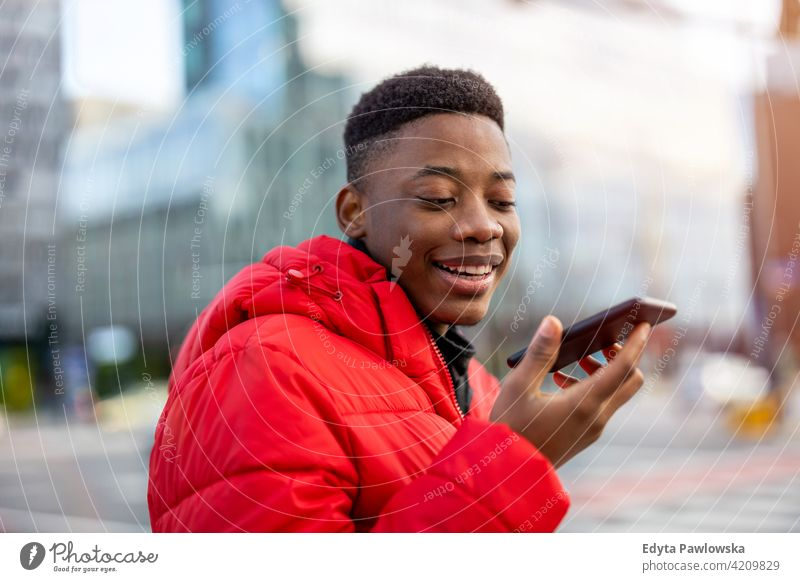 Young man using smart phone outdoors at urban setting black outside street millennial standing African city Warsaw real people casual lifestyle guy attractive