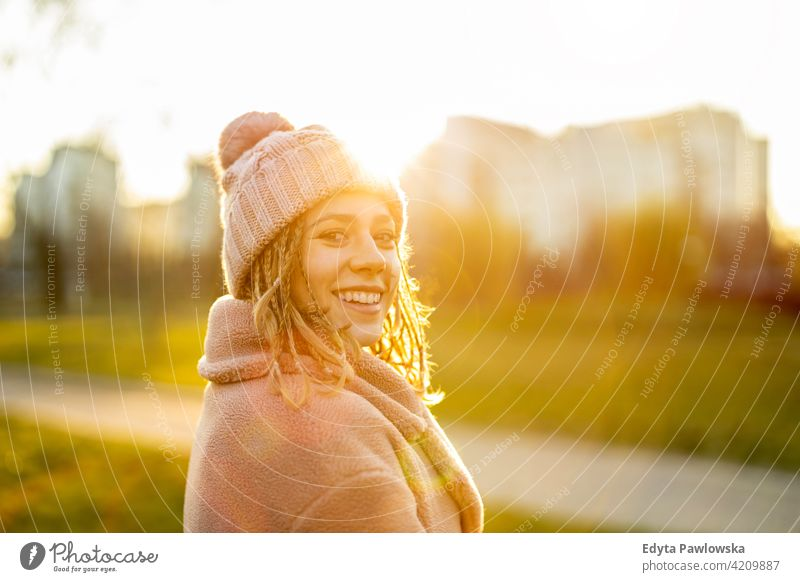 Playful young woman with braided hair outdoors millennial rebel braids urban city street teenage trendy cool warm clothes winter style fall one autumn person