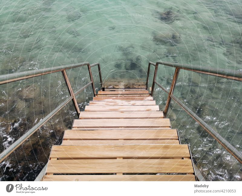 Bathing steps in sunshine with clear water in the bay of Alacati near Cesme at the Aegean Sea in the province Izmir in Turkey swimming ladder Bathroom stairs