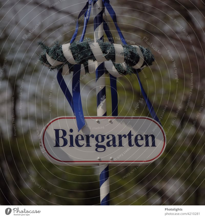"""Sign """"Biergarten"""" is attached to a maypole with a wreath and blue ribbons. May tree Beer garden sign Wreath tapes Blue Green White Deserted Colour photo"""