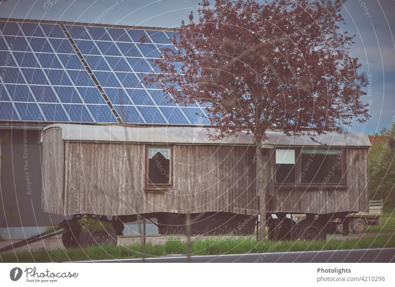 Wooden caravan stands in front of a barn with solar roof. Flowering tree in the foreground. Site trailer Trailer Caravan Barn Drape Wheels trailer coupling Tree