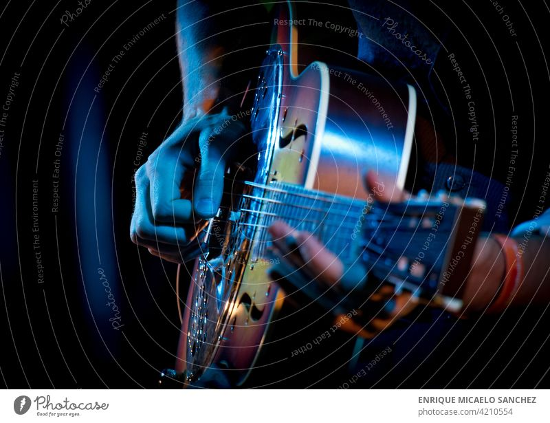 Guitarist playing dobro guitar live electric jazz event concert player entertainment rock band festival outside singer acoustic blues pop garden adult stand up