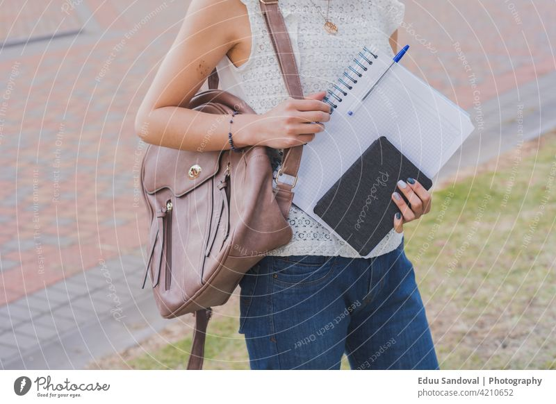 Young woman in glasses with notebooks for her studies. college young girl latin happy study student teenage smile fine-looking beauty preparation cute portrait