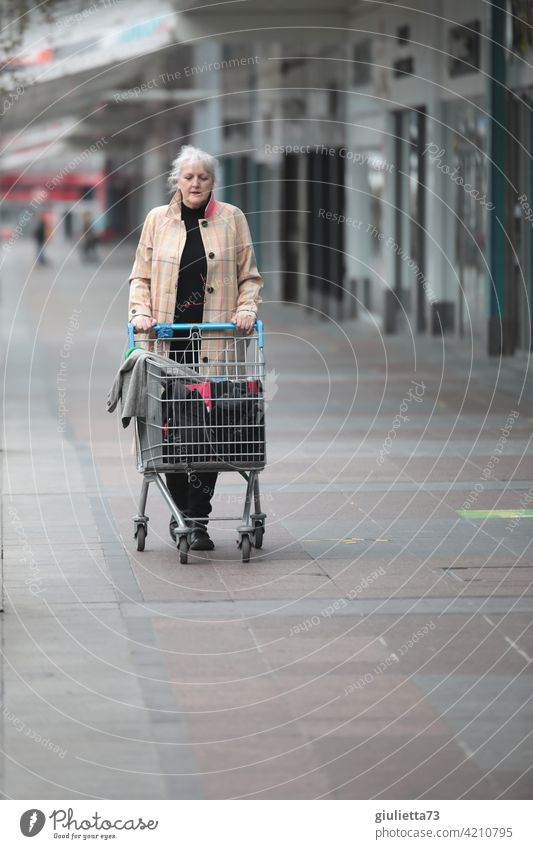 Woman with coat and shopping cart on lonely shopping stroll Coat Human being portrait Exterior shot Adults Loneliness Shopping Trolley Shopping malls