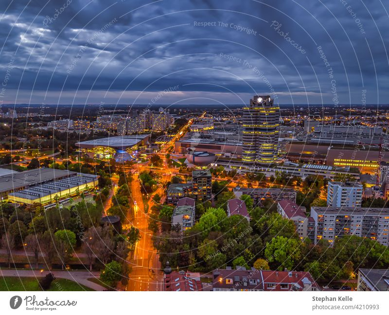 Wonderful twilight view over the illuminated Munich with business district and cars on a road from a high perspective. german southern germany top bavarian