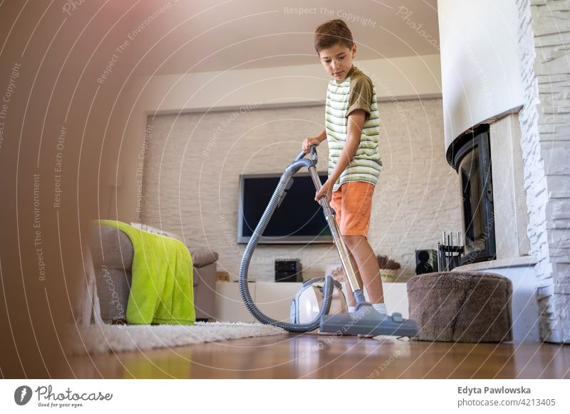 Boy vacuuming floor at home vacuum cleaner housework chores helping learning family people child son boy kid kids children lifestyle elementary offspring