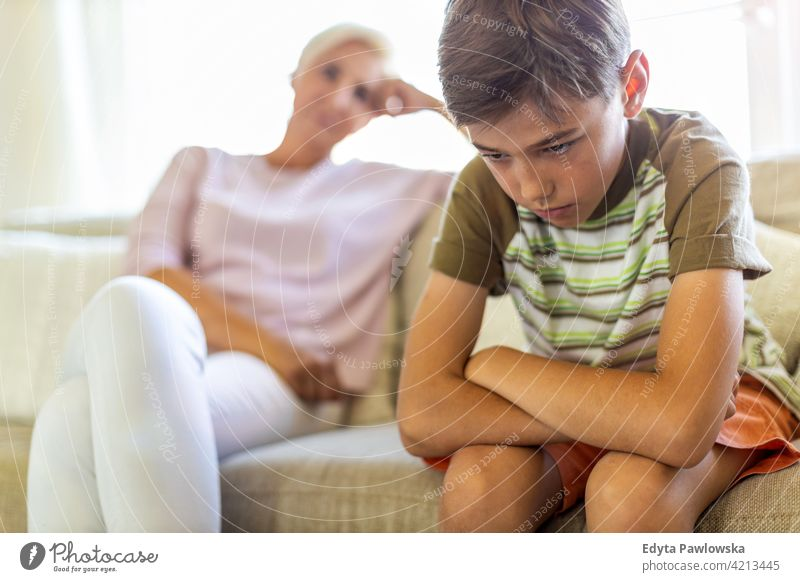 Angry boy and frustrated mother sitting on sofa upset argue angry problem teenager conflict arguing serious attitude child son resentful stress frustration