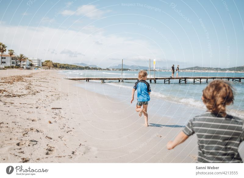 running children at the beach of Port de Alcudia Beach Ocean Sand Water Nature Sun Waves Sky Vacation & Travel Beautiful weather Exterior shot Relaxation