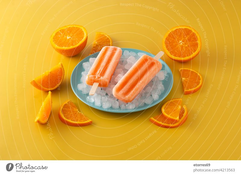 Orange popsicles on blue plate background cake cold colorful cool cream dessert flavor food fresh frosty frozen fruit homemade ice icecream iced juice lolly