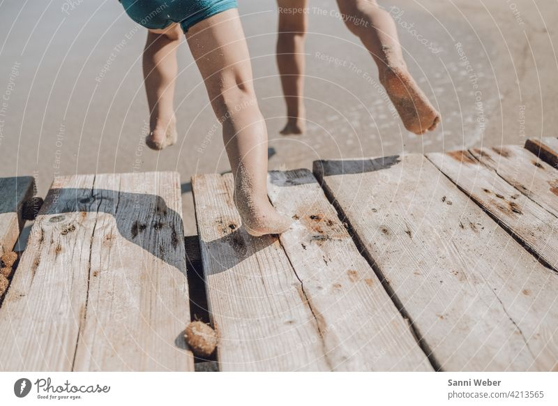 Children jump from the jetty into the water children Infancy Playing Joy Nature Beach Happiness Happy Exterior shot Colour photo Vacation & Travel feet Jump