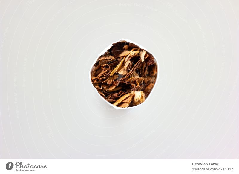Single unlit cigarette stick macro detail shot of ground tobacco leafs front view isolated on white illness addictive filtered costly new one expensive single