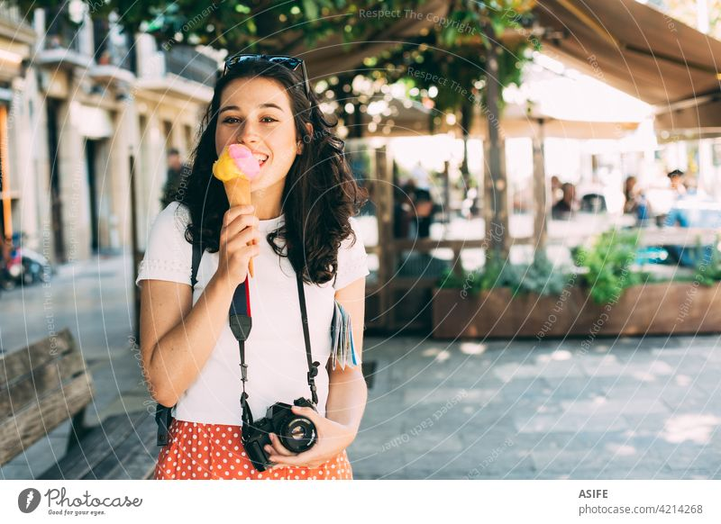 Happy young beautiful tourist woman enjoying a big ice cream eating scoop cone happy travel vacation refreshment holiday snack food city backpack camera summer