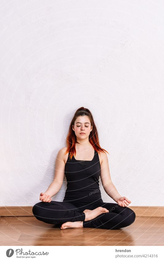 woman practices yoga and meditates in the lotus position meditating meditation exercise relaxation fitness pose mind peace wellness peaceful young adult freedom