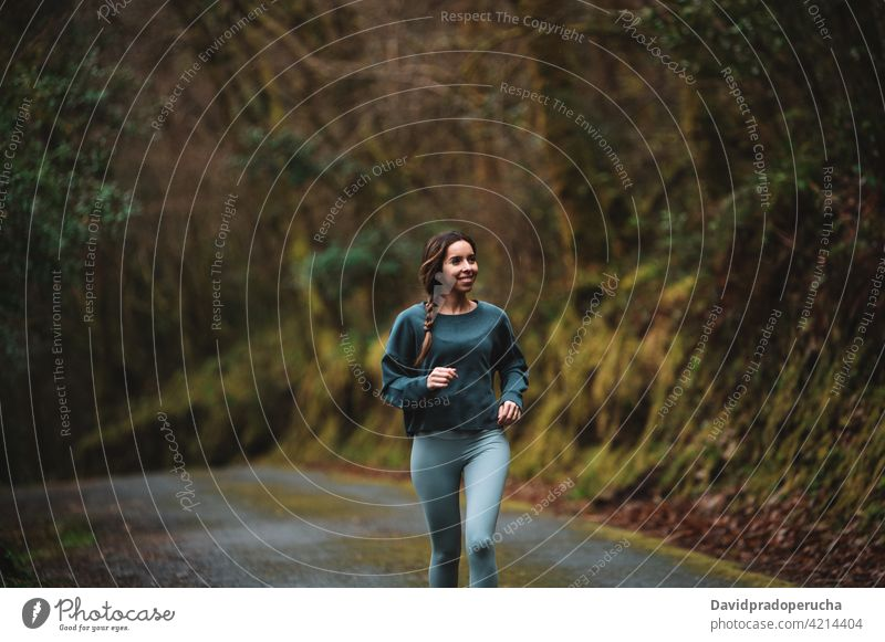 Woman running along road in forest sportswoman training runner cardio move workout active energy female woods sportswear athlete activity healthy slim wellbeing