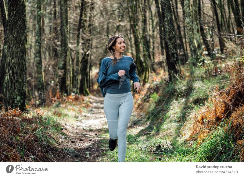 Sporty woman running in forest sporty active training fitness activewear workout woods activity runner sportswoman jog healthy path trail wellness jogger