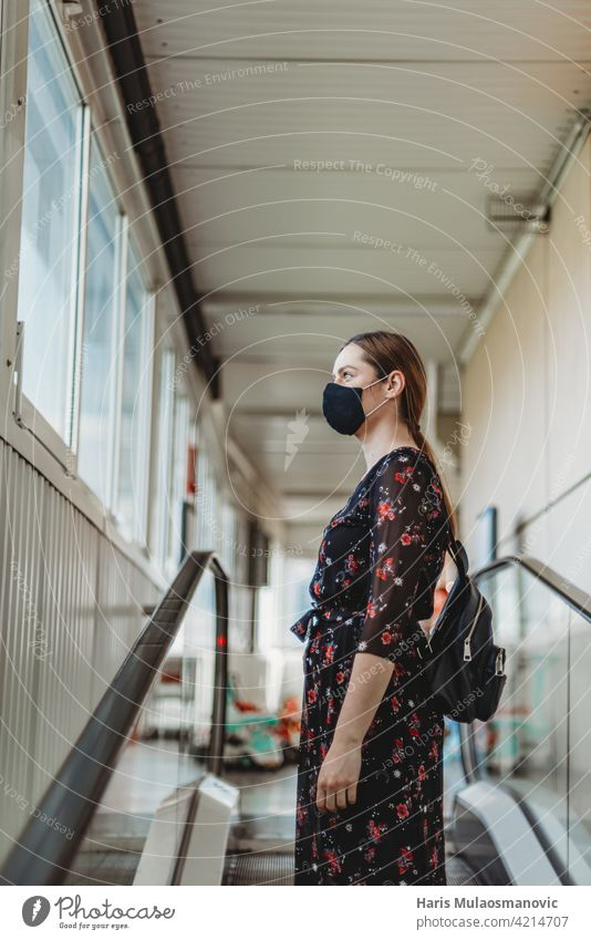 woman with face mask standing on moving escalator adult attractive beautiful beauty business casual caucasian city coronavirus covid 19 entrance fashion female