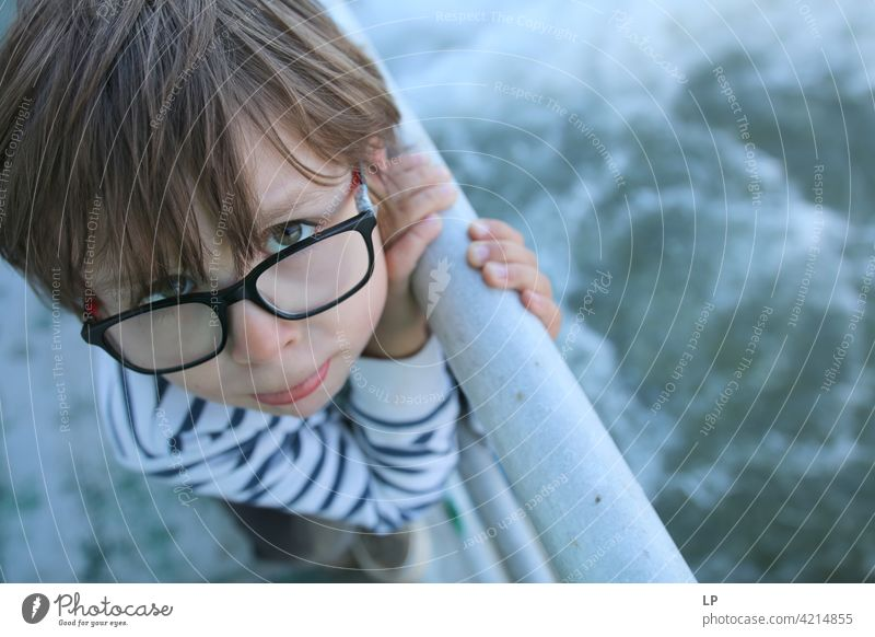Child wearning glasses making a face looking upwards hesitant puzzled Perplexed sceptical doubts doubtful Doubt hestitate uncertainty confusion Infancy reality