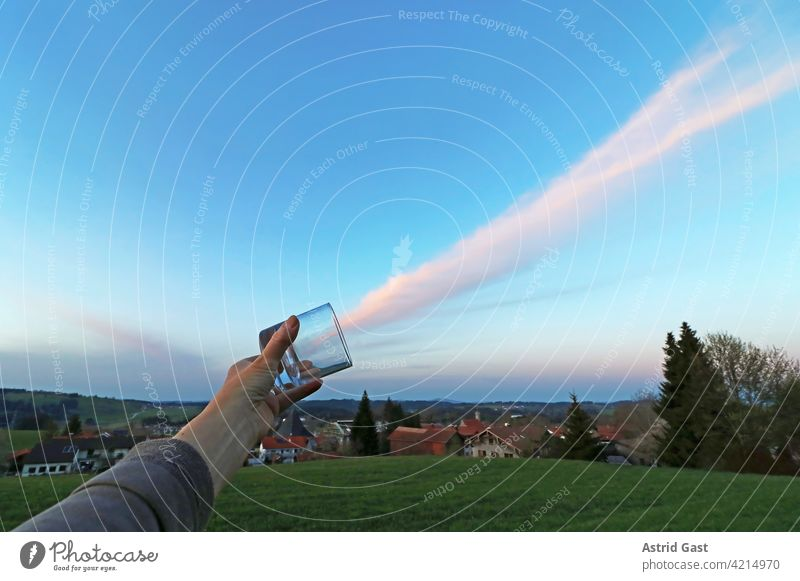Cloud catching. A woman holds a glass in the evening sky go a cloud Sky Glass Catch cloud catching Weather affect the weather Evening Woman Hand stop Capture