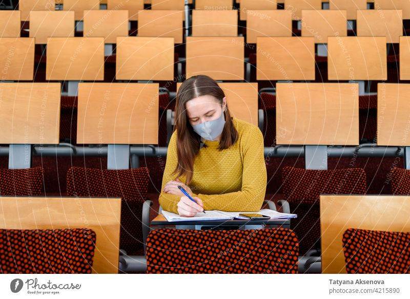 Woman student sitting in face mask education classroom studying back to school high school learning safety woman person indoors protection social distancing