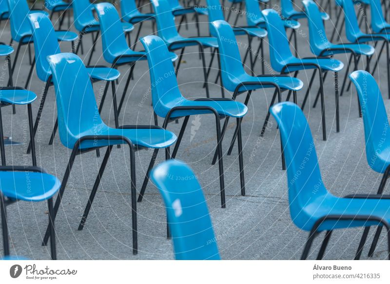 Rows and columns of nondescript blue plastic chairs, consecutive, arranged in a line, at similar intervals of space, facing the same place. Retiro Park, Madrid, Spain.