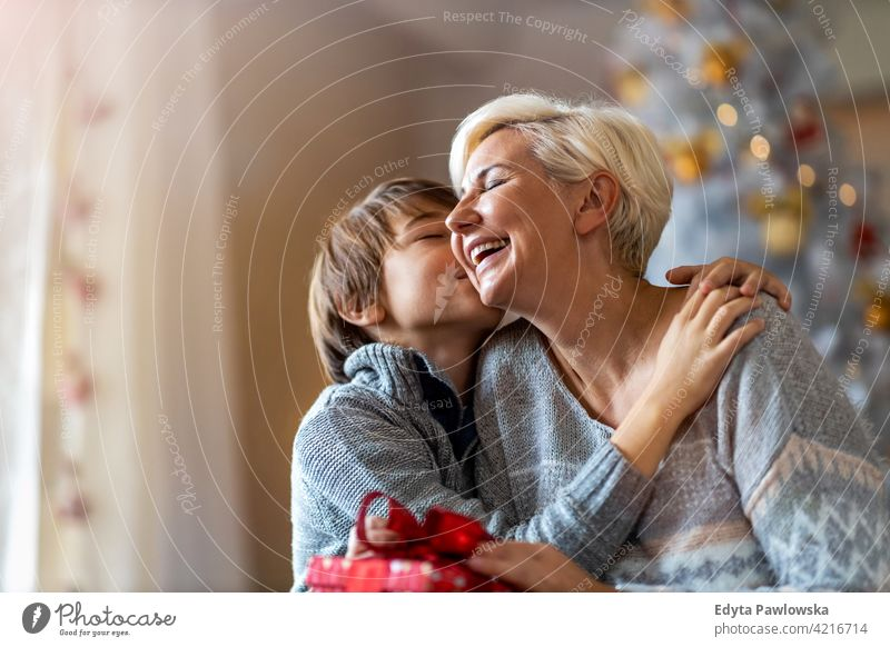 Son giving mother Christmas gift son boy child children kids hugging embracing winter christmas christmas tree lifestyle indoors happy people Caucasian fun joy