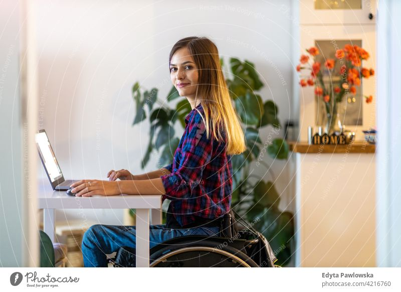 Woman in wheelchair using laptop at home domestic life disability disabled confidence woman independent indoors house people young adult casual female Caucasian