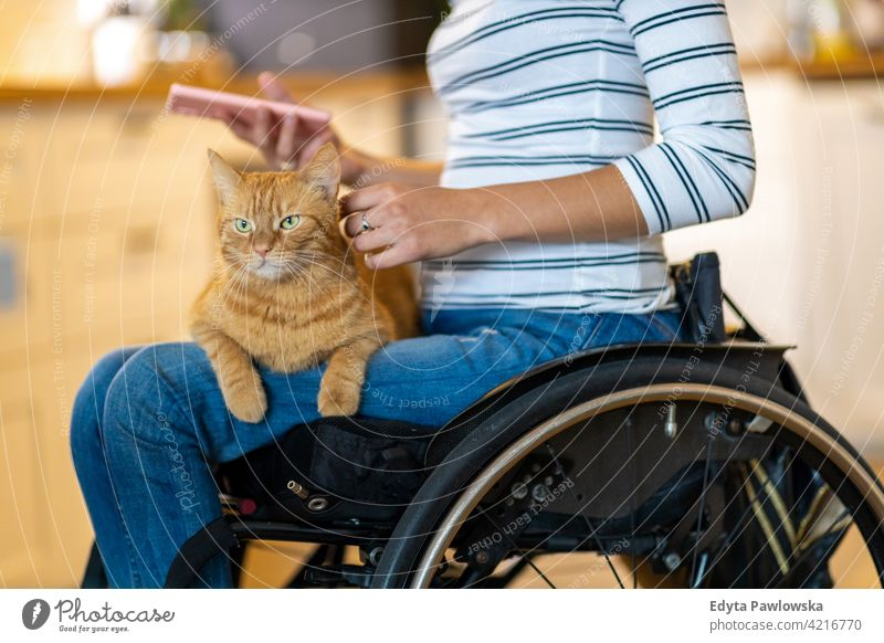 Woman in wheelchair with cat on her lap domestic life disability disabled confidence woman independent indoors home house people young adult casual female