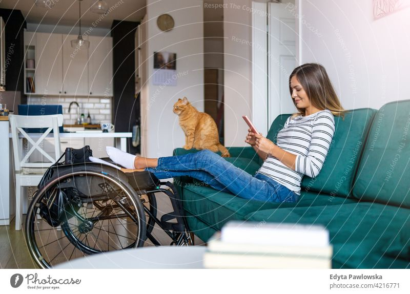 Disabled young woman using smartphone while sitting on sofa at home wheelchair domestic life disability disabled confidence independent indoors house people