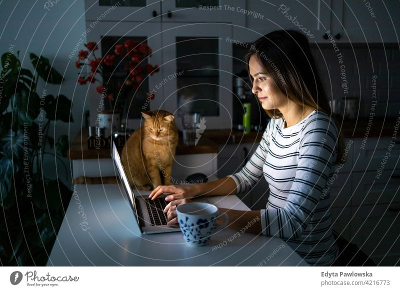 Concentrated woman working late hours with her laptop wheelchair domestic life disability disabled confidence independent indoors home house people young adult