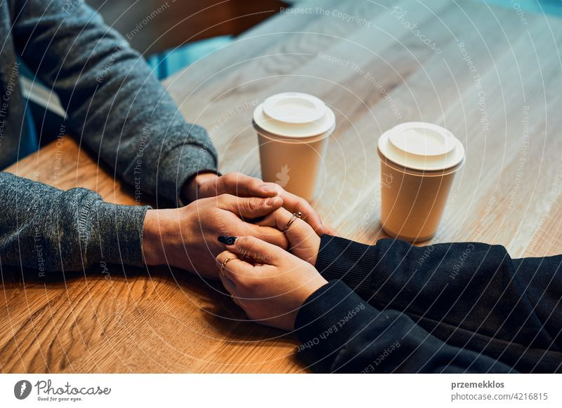 Loving couple holding hands sitting in cafe  drinking coffee man restaurant caucasian indoors shop coffee shop inside hot cup lifestyles espresso mug break