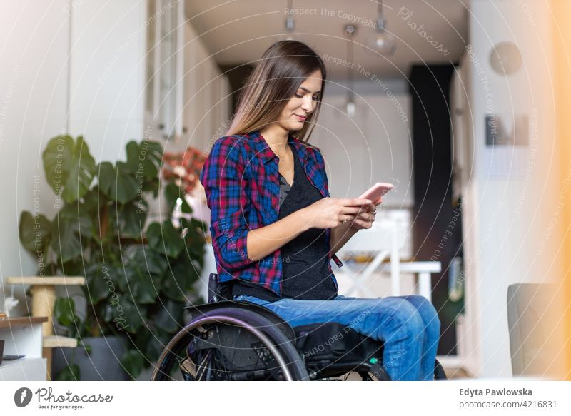 Woman In Wheelchair on Smartphone At Home wheelchair domestic life disability disabled confidence woman independent indoors home house people young adult casual