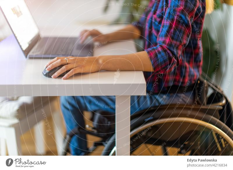 Woman in wheelchair using laptop in office domestic life disability disabled confidence woman independent indoors home house people young adult casual female