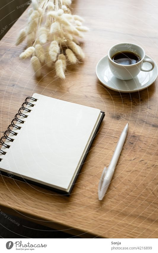 An empty notepad, a ballpoint pen and a cup of coffee on a wooden table Notebook Coffee Ballpoint pen at home Wooden table Paper Tabletop Feminine Cup Diary